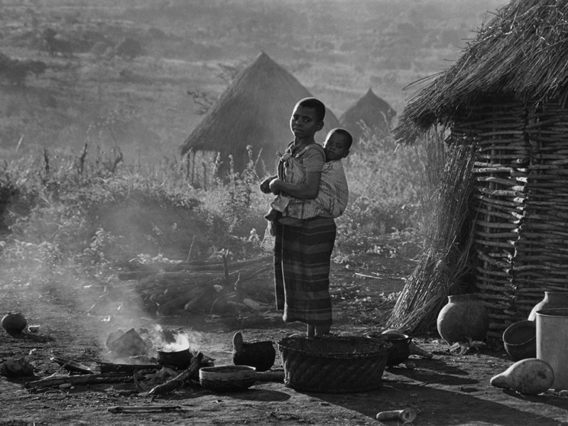 Mozambique, Espungabera.1985. A girl carries her baby brother while preparing a meal at sunset.