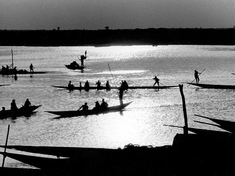 Mali, Mopti. 1986. Rowers navigate their canoes with cargo and passengers across the river Niger at sunset.