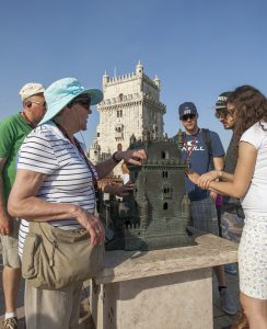 Portugal, Lisbon, Belém. 2016. Visually handicapped tourists experience the maquette of the Tower of Belém on display next to the monument itself.