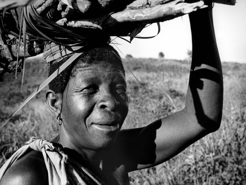 Mozambique, Manica province, Espungabera.1985. An elderly woman returns to her house carrying fire wood.