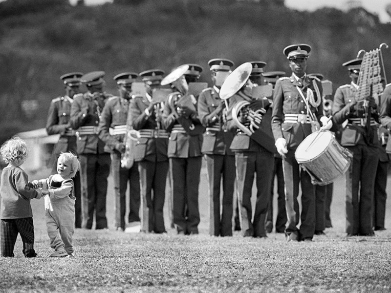 Zimbabwe, Domboshawa. 1989. A military band plays while two little children dance on the lawn.