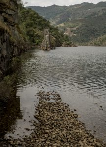 Portugal, Alto Douro. 2017. View at the River Tua valley near the former railway station of São Lourenço (marker 15) where the railway is being submerged with the ballast just slipping beneath the water.
